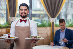 Attractive young waiter is working at restaurant Royalty Free Stock Photos