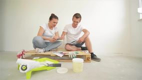 Attractive Young Wife with Her Husband Sitting on the Floor with Palette in Hands and Choosing Colors for Their New stock footage