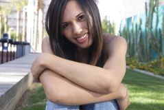 Attractive Young Woman. With arms crossed over her knees stock photos