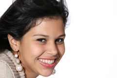 Attractive young woman. Cute young Hispanic woman wearing a beige sweater her long black hair flying Stock Image