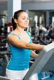 Attractive young woman adjusts the treadmill Royalty Free Stock Photo
