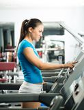 Attractive young woman adjusts the treadmill Royalty Free Stock Photography