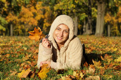 Attractive young woman against autumn leaves. Outdoor shot stock images