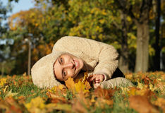 Attractive young woman against autumn leaves. Attractive young woman lying against autumn leaves. Outdoor shot royalty free stock image