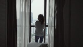 Woman at the Window. Attractive young woman alone with her thoughts standing by the window at home stock footage