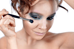 Attractive young  woman applying blusher Stock Photo