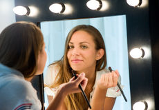 Attractive young woman applying her makeup Royalty Free Stock Photography