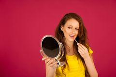 Attractive young woman applying lip gloss looking in mirror over Royalty Free Stock Photo
