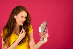 Attractive young woman applying lip gloss looking in mirror over Stock Image