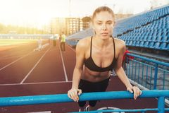 Attractive young woman athlete doing plank exercise on stadium. Attractive young woman athlete wearing in the dlck sport top doing plank exercise on stadium with royalty free stock images