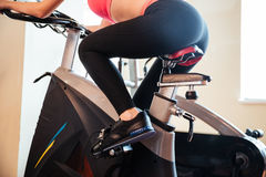 Attractive young woman athlete training in gym using bicyle. Back view of attractive young woman athlete training in gym using bicyle Stock Photos
