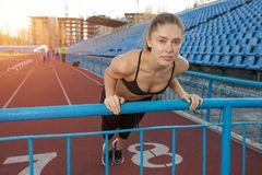 Attractive young woman athlete doing plank exercise on stadium. Attractive young woman athlete wearing in the black sport top doing plank exercise on stadium stock photo