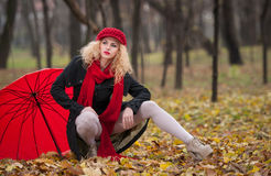 Attractive young woman in a autumn fashion shoot. Beautiful fashionable young girl with red accessories outdoor Royalty Free Stock Photos