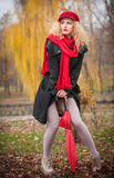 Attractive young woman in a autumn fashion shoot. Beautiful fashionable young girl with red accessories outdoor Stock Photo