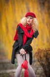 Attractive young woman in a autumn fashion shoot. Beautiful fashionable young girl with red accessories outdoor Stock Images