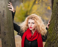 Attractive young woman in a autumn fashion shoot. Beautiful fashionable young girl with red scarf in the park. Blonde women Stock Photo