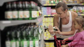 Attractive young woman with baby daughter selecting a drinks in supermarket. stock footage