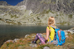 Attractive young woman backpacker relaxing near mountain lake Royalty Free Stock Photo