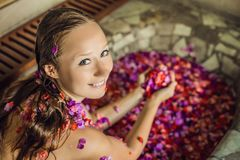Attractive Young woman in bath with petals of tropical flowers and aroma oils. Spa treatments for skin rejuvenation stock photo