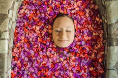 Attractive Young woman in bath with petals of tropical flowers and aroma oils. Spa treatments for skin rejuvenation stock photography