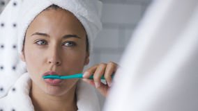 Attractive young woman in the bathroom brushing her teeth in front of the mirror Stock Photo