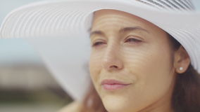 Attractive young woman on the beach adjusting her white sun hat before enjoying the view stock footage