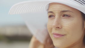 Attractive young woman on the beach adjusting her white sun hat before enjoying the view, in slow motion stock video footage