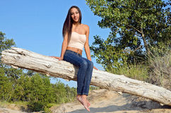 attractive young woman on beach log Stock Photo