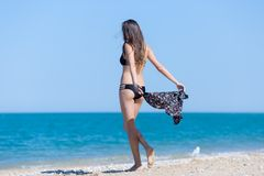 Girl in bikini goes to water, dropping robe on go Royalty Free Stock Photography