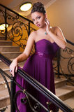 Woman in a beautiful dress sloit on the stairs Royalty Free Stock Image
