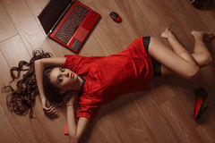 Attractive young woman with a beautiful face relaxes on wooden floor stock photography