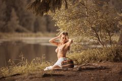 Attractive young woman with beautiful long blond hair sitting topless. Attractive young woman with beautiful gold long hair sitting topless by the lake at sunset