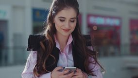Attractive young woman with beautiful make-up in the pink shirt is in the shopping center. She is smiling and texting a. Message. Close up view stock video