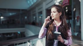 Attractive young woman with beautiful make-up in the pink shirt is walking in the shopping center with a cup of coffee. She is talking on her smartphone. Close stock video