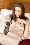 Attractive young woman in bed binge eating Royalty Free Stock Images