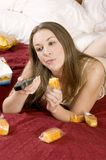 Attractive young woman in bed binge eating Stock Photo