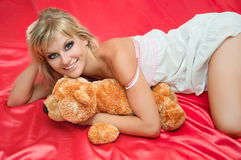 Attractive young woman on a bed on pink Royalty Free Stock Images