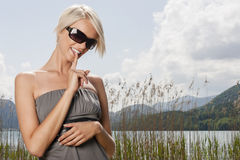 Attractive young woman at Bergsee. Attractive young blond woman in sunglasses and a stylish strapless summer dress standing in front of the lake at Bergsee Royalty Free Stock Photos