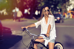 Attractive young woman on a bicycle in a city Royalty Free Stock Photo