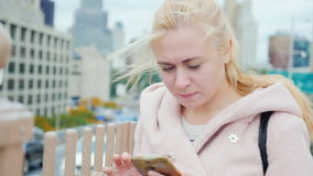 Attractive young woman in the big city. It use the phone in an urban style. New York, Manhattan, USA. Portrait of a young woman in New York. It should be in the stock video