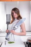 Attractive young woman with big fork and knife Stock Images
