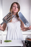 Attractive young woman with big fork and knife Royalty Free Stock Photography