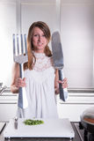 Attractive young woman with big fork and knife Royalty Free Stock Photos