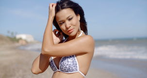 Attractive young woman in a bikini on a beach. Attractive young woman in a bikini on a tropical beach standing looking at the camera with her hands to her hair stock footage