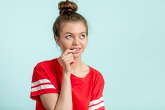 Attractive young woman biting her nails while thinking and looking up. On the isolated white background. close up side view photo. copy space stock photo