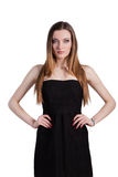 Attractive young woman in a black dress smiling and looking at c. Amera Royalty Free Stock Image