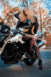 Attractive young woman in black leather outfit with classic style motorcycle stock photography
