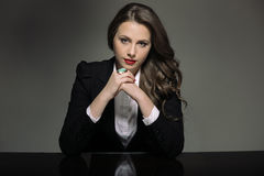 Attractive young woman in a black suit sitting at the table Stock Photo