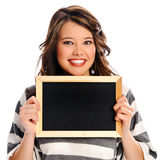 Attractive young woman with blank sign. Young beautiful girl holds a empty chalkboard for you to fill in your message Stock Photography