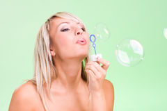 Attractive young woman blowing bubbles Stock Photos